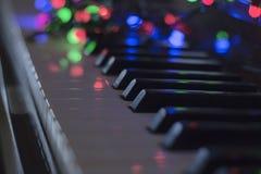 Guirnalda de la Navidad con las luces en un piano electrónico - decoración para la celebración de la Navidad y del Año Nuevo Imagenes de archivo