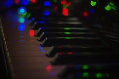Guirnalda de la Navidad con las luces en un piano electrónico - decoración para la celebración de la Navidad y del Año Nuevo Foto de archivo
