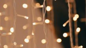 Guirnalda de la Navidad con las luces de oro, en primer de la alameda Luces de la Navidad borrosas en centro comercial Bokeh metrajes