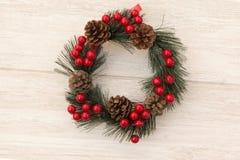 Guirnalda de la Navidad con los conos del pino y las bayas rojas Foto de archivo libre de regalías