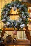 Guirnalda de la Navidad con los conos y los juguetes de la Navidad en una estructura de madera foto de archivo