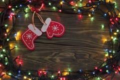 Guirnalda de la Navidad con un guante que brilla intensamente y los calcetines Imagen de archivo libre de regalías
