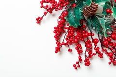 Guirnalda de la Navidad de las bayas y del árbol de hoja perenne del acebo aislados en el fondo blanco Fotos de archivo