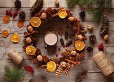 Guirnalda de la Navidad de las ramas y de los conos del pino, adornada con la naranja escarchada, nueces, canela en la tabla viej Fotos de archivo