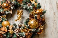 Guirnalda de la Navidad hecha de árbol de abeto y adornada en tonos de oro Imagen de archivo libre de regalías