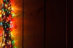 Guirnalda de la Navidad que brilla intensamente en el fondo de madera en la oscuridad imagenes de archivo