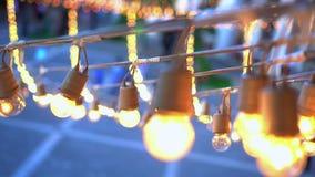 Guirnalda de las bombillas del festival que cuelga sobre lugar del acontecimiento almacen de metraje de vídeo
