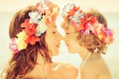 Guirnalda de las flores del hawaiian de la mujer que lleva y del niño foto de archivo libre de regalías