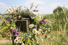 Guirnalda de las flores que cuelgan en un palillo de madera en un campo salvaje Imagenes de archivo