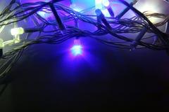 Guirnalda de las luces de la Navidad en un fondo oscuro fotografía de archivo