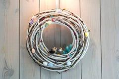 Guirnalda de Pascua hecha de los huevos y de los p?jaros de las ramitas en fondo de madera de la pared fotos de archivo libres de regalías