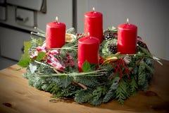 Guirnalda del advenimiento con la quema de velas rojas Fotos de archivo libres de regalías