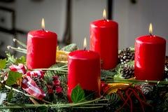 Guirnalda del advenimiento con la quema de velas rojas Fotografía de archivo