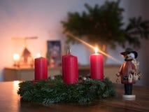 Guirnalda del advenimiento con una vela encendida Foto de archivo