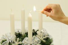 Guirnalda del advenimiento de la Navidad - la mano enciende la vela Fotos de archivo