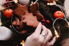 Guirnalda del ` s del Año Nuevo con las galletas del pan de jengibre para el partido de Navidad La mano del ` s de la mujer puso  Imagen de archivo libre de regalías