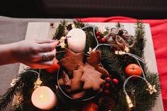 Guirnalda del ` s del Año Nuevo con las galletas del pan de jengibre para el partido de Navidad La mano del ` s de la mujer puso  Fotografía de archivo