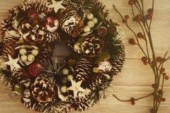 Guirnalda delicada de la Navidad de los conos del pino en fondo de madera Foto de archivo libre de regalías