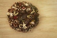 Guirnalda delicada de la Navidad de los conos del pino en fondo de madera Imagenes de archivo