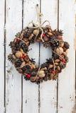 Guirnalda en el backround oxidado blanco del tablero de madera, guirnalda natural de la Navidad de la decoración, vertical Imagenes de archivo
