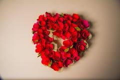 Guirnalda en forma de corazón en fondo rosado Imagenes de archivo