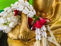 Guirnalda floral en las manos de la estatua de Buda Foto de archivo libre de regalías