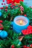 Guirnalda hermosa de la Navidad, vela azul, bayas Foto de archivo libre de regalías