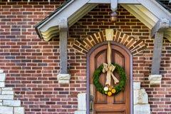 Guirnalda imperecedera en una puerta sólida del roble con las pequeñas calabazas anaranjadas y blancas Fotografía de archivo libre de regalías