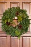 Guirnalda imperecedera verde de la Navidad en puerta de madera Imagen de archivo libre de regalías
