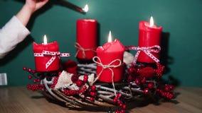 Guirnalda moderna de la Navidad con cuatro velas rojas en superficie de madera con el fondo verde metrajes