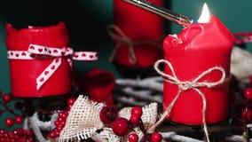 Guirnalda moderna de la Navidad con cuatro velas rojas en superficie de madera con el fondo verde almacen de video