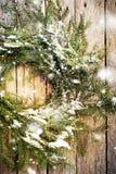 Guirnalda natural verde con nieve en fondo de madera Se dibuja la nieve que cae Foto de archivo libre de regalías