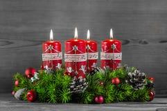 Guirnalda o corona del advenimiento con cuatro velas rojas en backgroun de madera Imagen de archivo