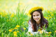 Guirnalda que lleva de la chica joven linda de dientes de león y de la sonrisa Fotos de archivo