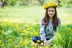 Guirnalda que lleva de la chica joven linda de dientes de león y de la sonrisa Imagen de archivo