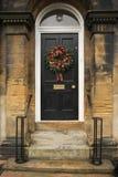 Guirnalda roja de la manzana y de los chiles en una puerta negra Foto de archivo libre de regalías