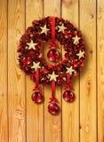 Guirnalda roja de la Navidad en puerta de madera Fotos de archivo libres de regalías