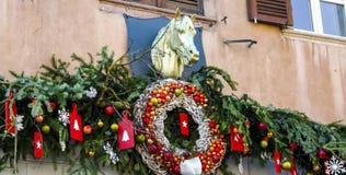 Guirnalda y decoraciones de la Navidad en fachada con la escultura del caballo imagen de archivo libre de regalías