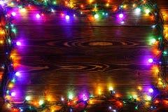 Guirnalda y guirnaldas de bombillas coloreadas Fondo de la Navidad con las luces y el espacio del texto libre Frontera de las luc Fotografía de archivo