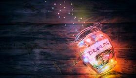 Guirnaldas de luces coloreadas en el tarro de cristal con sueños Foto de archivo libre de regalías
