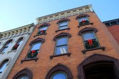 Guirnaldas del día de fiesta que adornan las ventanas de edificios viejos Imágenes de archivo libres de regalías
