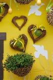 Guirnaldas, pájaros y pensamientos en forma de corazón en la cesta en la pared amarilla foto de archivo libre de regalías