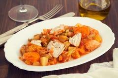 Guisado de turquia com os vegetais no prato branco no fundo de madeira Foto de Stock