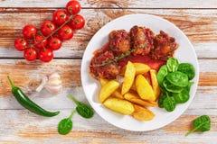 Guisado do rabo de boi com salada fritada da batata e dos espinafres Imagens de Stock
