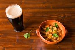 Guisado irlandés tradicional con una pinta de la cerveza valiente y de un trébol Imagen de archivo
