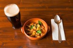 Guisado irlandés tradicional con una pinta de la cerveza valiente y de una cuchara Imágenes de archivo libres de regalías
