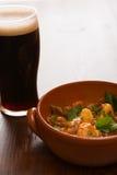 Guisado irlandés tradicional y una pinta de cerveza en retroiluminado Imagen de archivo libre de regalías