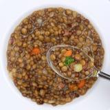 Guisado sano de la sopa de lenteja de la consumición con las lentejas en la cuchara desde arriba Fotografía de archivo libre de regalías