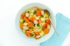Guisado vegetal con la salchicha cortada en cuenco de sopa azul Imagenes de archivo