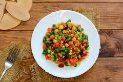 Guisado vegetal misturado em uma placa do serviço e em uma tabela de madeira Cenouras cozidos caseiros, feijões verdes, feijões v Fotos de Stock